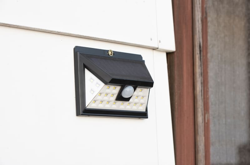 solar flood light mounted in a white wall